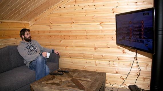 De tre barnen kräver tv, så på andra våningen finns det ett eget tv-rum framför plattskärmen. Det svarta röret bakom tvn är skorstensröret som leder värme från vedspisen i bottenplanet.