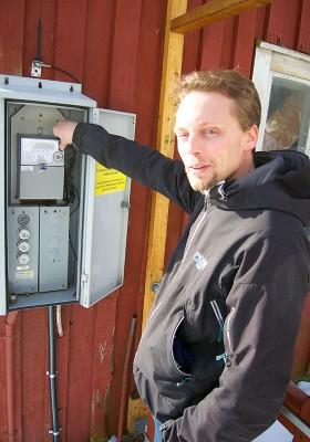 Andreas Molin visar stolt upp mätarskåpet med en elmätare som går baklänges i vårsolen.